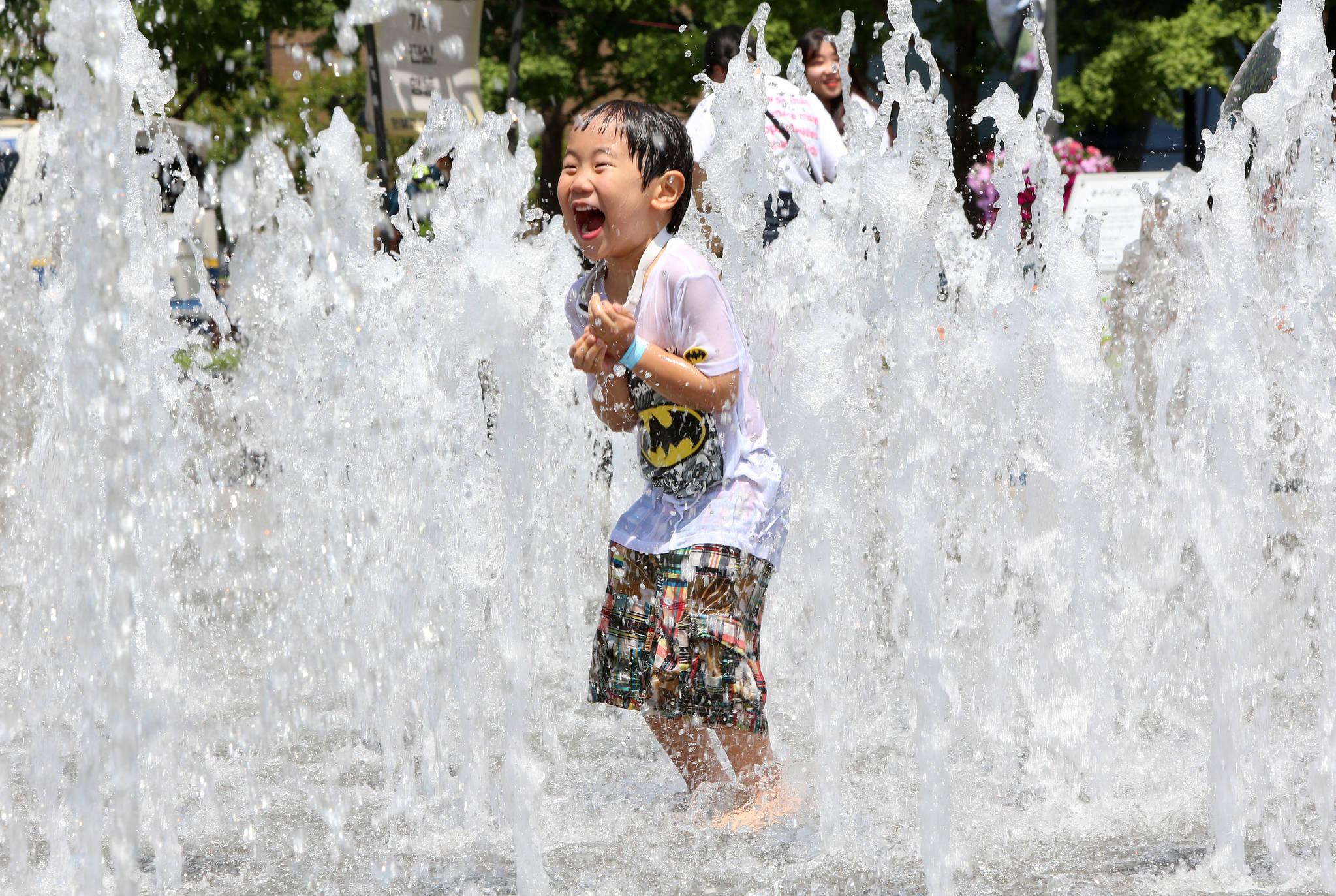 5일 오후서울 광화문 광장에서 한 어린이가 분수대 물을 맞으며 더위를 식히고 있다.조문규 기자