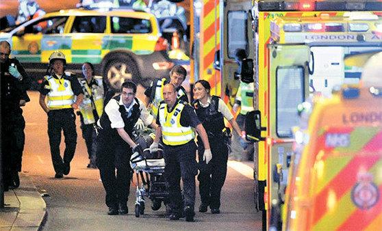 3일(현지시간) 테러가 발생한 영국 런던에서 경찰과 구급대원들이 부상자를 후송하고 있다. 이날 런던브리지 일대에서 차량과 흉기를 이용한 연쇄 테러로 최소 7명이 숨지고 48명이 다쳤다. [AFP=연합뉴스]