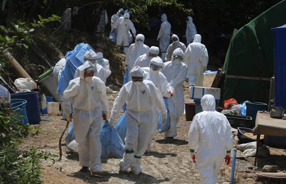 방역 대원들이 5일 부산 기장군의 한 농가에서 살처분한 닭 등을 매몰지로 옮기고 있다. [송봉근 기자]