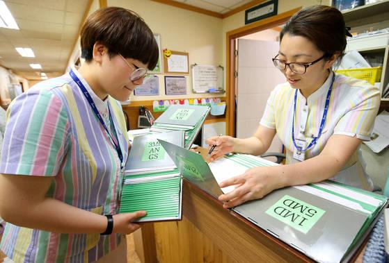 지난 1일 전남 고흥군의 병원 5층 병동에서 응급구조사(왼쪽)와 간호사가 함께 환자 의료 차트를 확인하고 있다. 간호사와 응급구조사의 복장은 색깔만 다를 뿐 큰 차이가 없다. 고흥=프리랜서 장정필