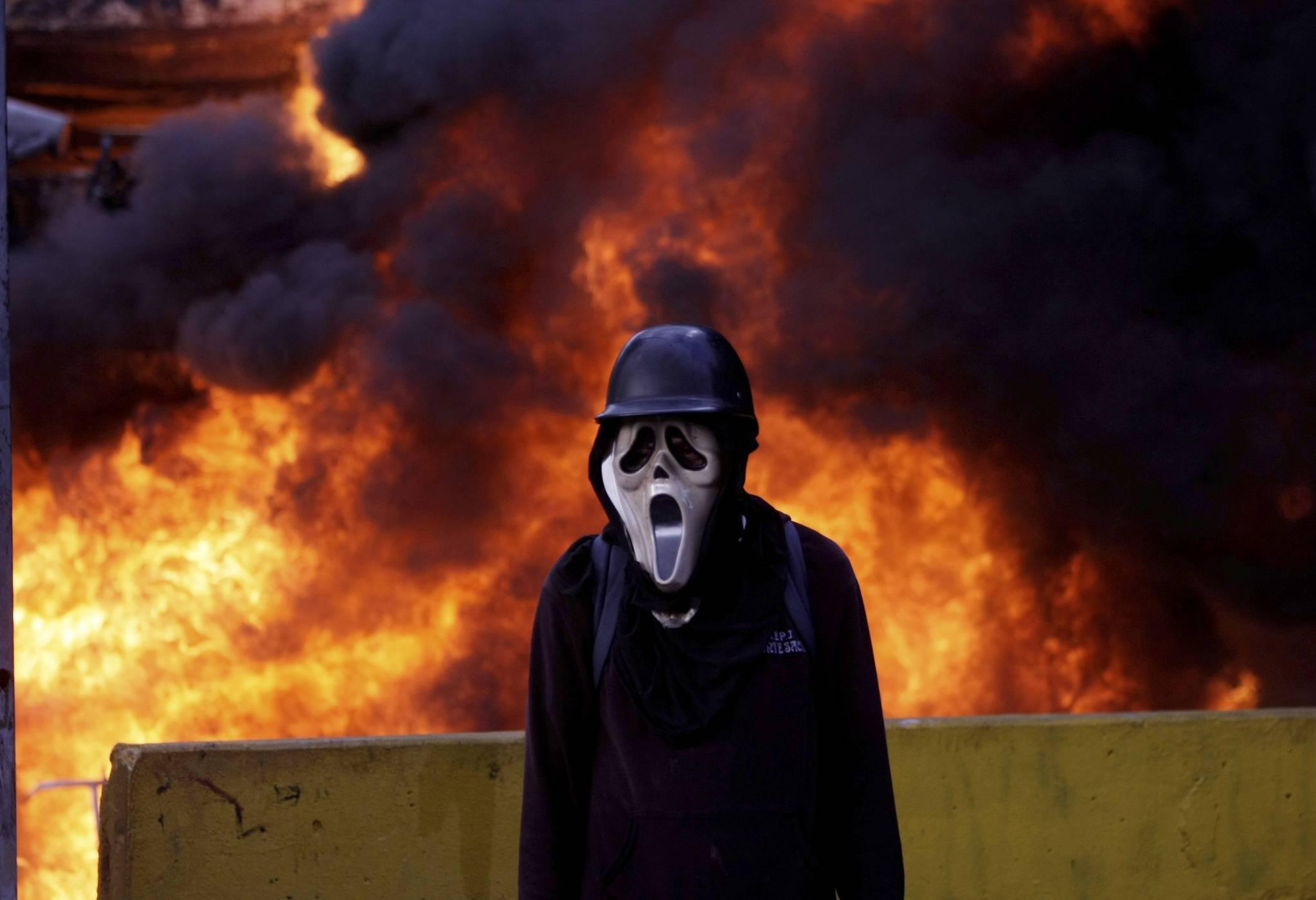 지난 5월27일(현지시간) 베네수엘라 카라카스 시내에서 마스크를 착용한 시위대가 보안군에 맞서고 있다.[AP=연합뉴스]