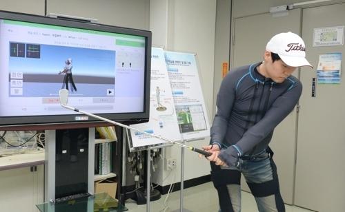 국내 연구진이 만든 실시간 모션 학습 옷을 입고 골프 샷 자세를 조정하는 모습. [ETRI 제공=연합뉴스]