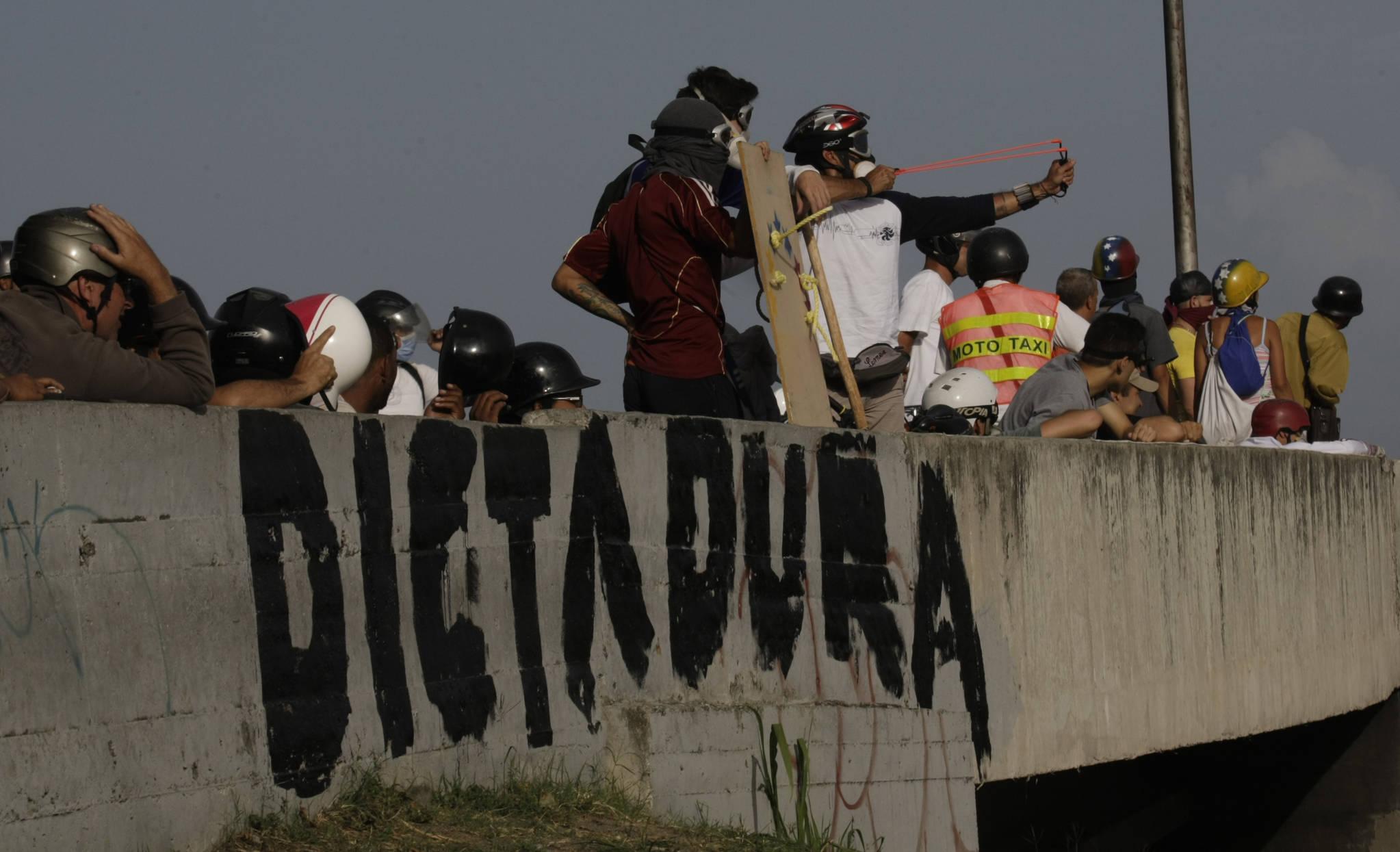 반정부 시위대가 지난 5월 31일(현지시간) 베네수엘라 카라카스에서 보안군을 향해 새총을 쏘고 있다.[AP=연합뉴스]