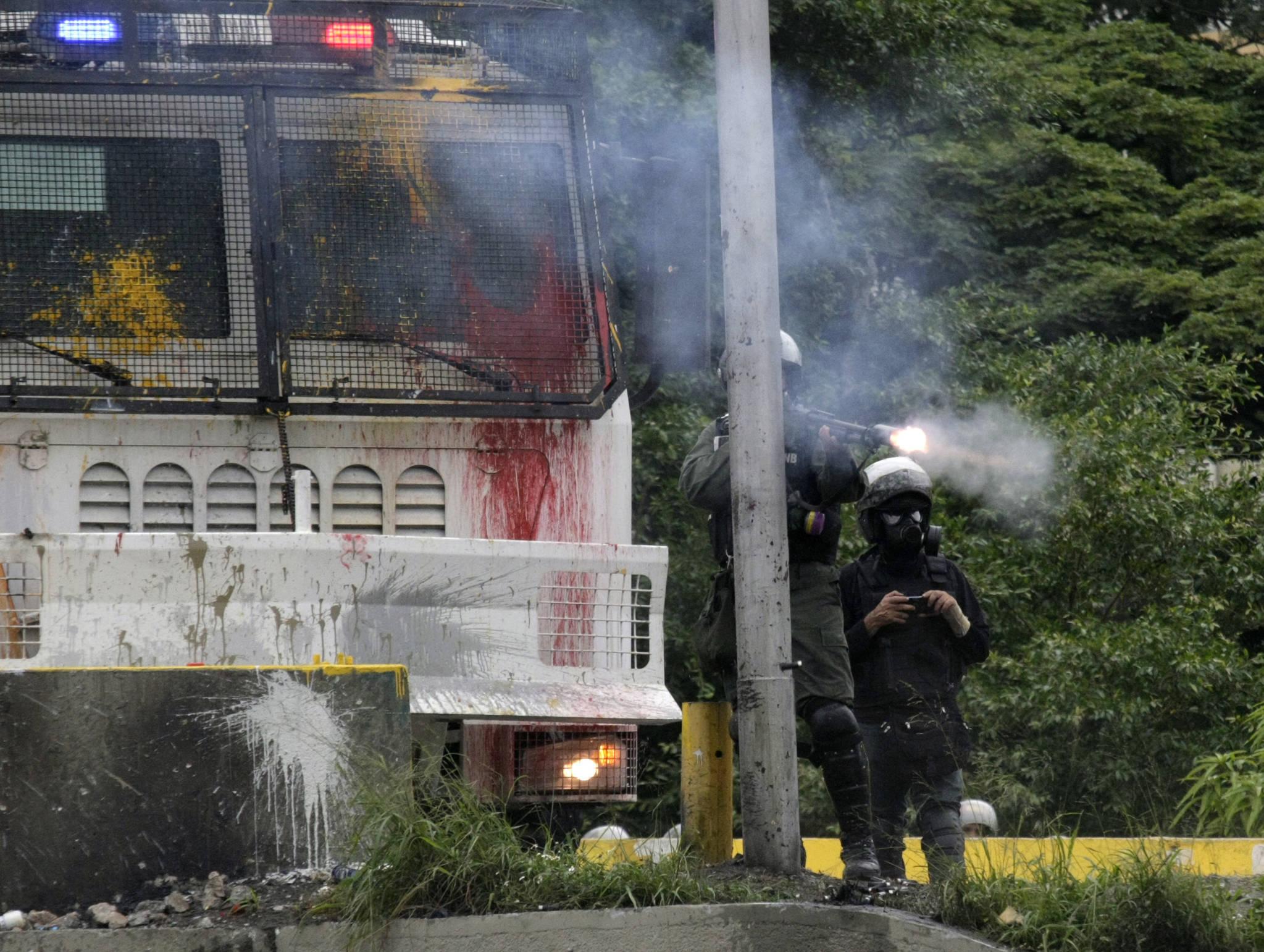 7일(현지시간) 베네수엘라 카라카스에서 경찰이 시위대를 향해 산탄총(shotgun)을 발사하고있다.[AP=연합뉴스]