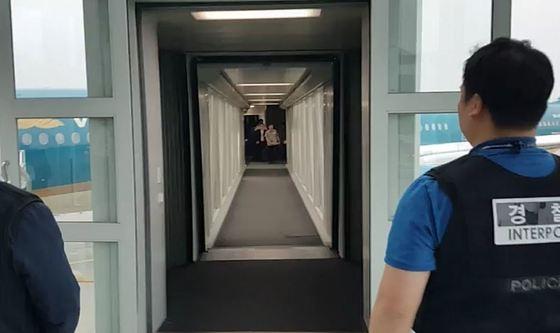 경찰 관계자들이 8일 인천공항에서 수배자 오모(31)씨 등 2명을 기다리고 있다. [사진 경찰청]