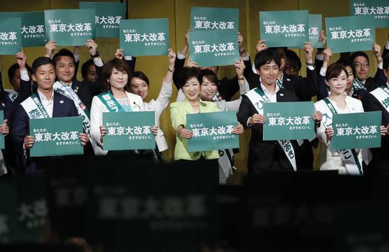 """지역 정당 도민퍼스트회 대표인 고이케 유리코 도쿄도 지사(가운데)가 1일 도쿄도 의회선거 총결기대회에 참석해 """"낡은 의회를 바꾸자""""며 입후보자들과 '도쿄대개혁'이 든 종이판을 들어 보이고 있다. [지지통신]"""