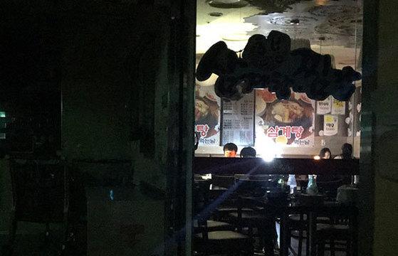 """11일 서울 구로구 신도림테크노마트의 한 식당에서 시민들이 비상등에 의지해 식사를 하고 있다. 이날 경기도 광명시와 서울 서남부 일대에서 낮 12시53분부터 26분간 대규모 정전이 발생했다. 한전 측은 """"경기 영서변전소의 기기 고장으로 전기 공급이 일시 중단됐다?며 ?신속하게 피해보상 할 것""""이라고 밝혔다. [연합뉴스]"""