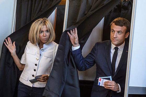 프랑스 총선 1차 투표가 실시된 11일 르 투케에서 에마뉘엘 마크롱 대통령(오른쪽)과 그의 부인 브리지트 트로노가 나란히 기표소를 나서고 있다. 이번 총선에선 마크롱이 창당한 '앙마르슈'의 압승이 예상된다. [르 투케 AP=연합뉴스]