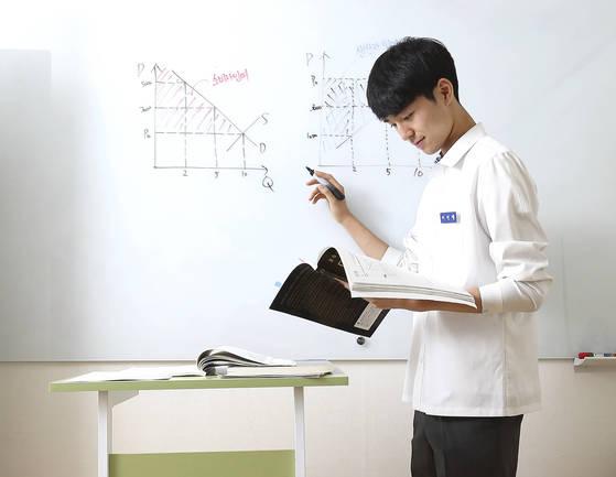 서울고 2학년 이민행군이 선 채로 학습하는 '스탠드 책상'에서 경제 공부를 하고 있다. 그는 집에있는 6개 책상을 옮겨 다니며 공부한다. [임현동 기자]