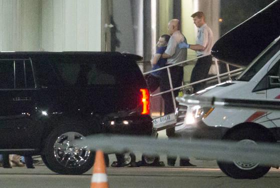 13일 항공편으로 오하이오주 신시내티 공항에 도착한 의식 불명 상태의 오토 웜비어를 의료진이 들어 올려서 차량으로 옮기고 있다. 웜비어의 코에는 튜브가 끼워져 있다. [AP=연합]