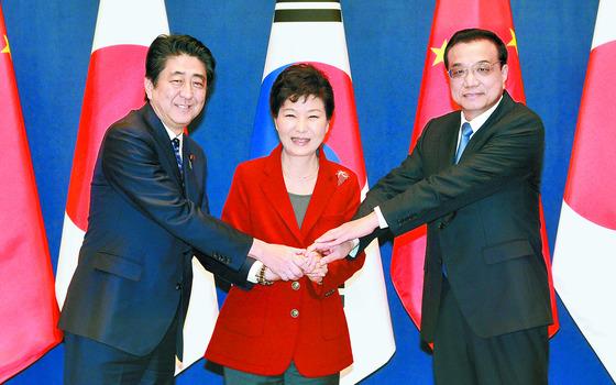 제6차 한·일·중 3국 정상회의가 2015년 11월 1일, 3년 반 만에 청와대에서 열렸다. 박근혜 대통령과 아베 신조 일본 총리(왼쪽), 리커창 중국 국무원 총리(오른쪽)가 손을 맞잡고 있다. 이날 3국 정상은 '동북아 평화협력을 위한 공동선언'을 채택했다. [청와대사진기자단]