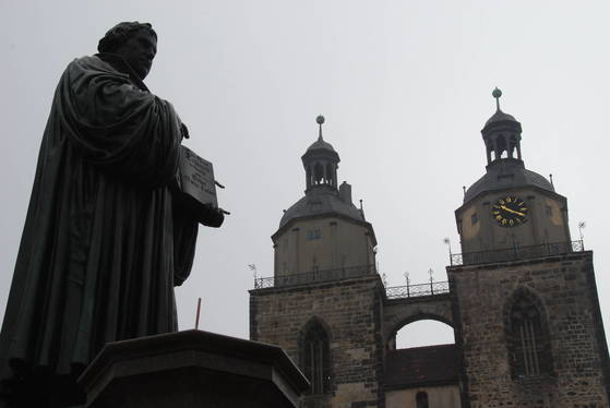 비텐베르크 교회 앞에 서 있는 마르틴 루터의 동상. 루터의 손에 라틴어에서 독일어로 직접 번역한 성경이 들려 있다. 백성호 기자