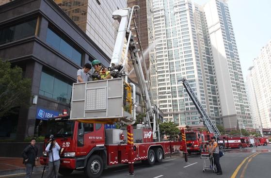 지난 2010년 10월 발생한 화재로 수십억원의 재산피해와 인명피해를 가져온 부산 해운대 마린시티 우신골든스위트. 해운대소방서가 고가사다리차를 이용해 화재진압과 인명구조 훈련을 하고 있다. [중앙포토]