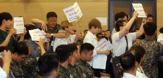 20일 오전 용산 국방컨벤션센터에서 장준규 육군참모총장이 육군력 포럼 축사를 하자 서강대학교 성소수자협의회원이라고 밝힌 학생들이 피켓 시위를 하고 있다.  '게이군인 마녀사냥 즉각 중단하라'고 쓰인 피켓을 든 10여명의 학생시위는 바로 제지됐다. <저작권자(c) 연합뉴스, 무단 전재-재배포 금지>