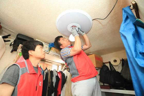 KT 직원들이 용산구 동자동 쪽방촌에 거주하는 한 노인의 집에 조명 모양의 '스마트 센서'를 설치하고 있다. [사진 서울시]