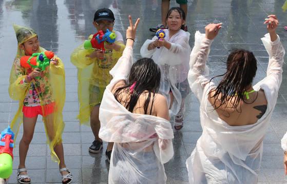 지난달 28일 부산 해운대해수욕장 입구 구남로 광장에서 열린 '게릴라 물총 서바이벌'행사 참가한 피서객들이 물총싸움을 하며 더위를 식히고 있다. 송봉근 기자