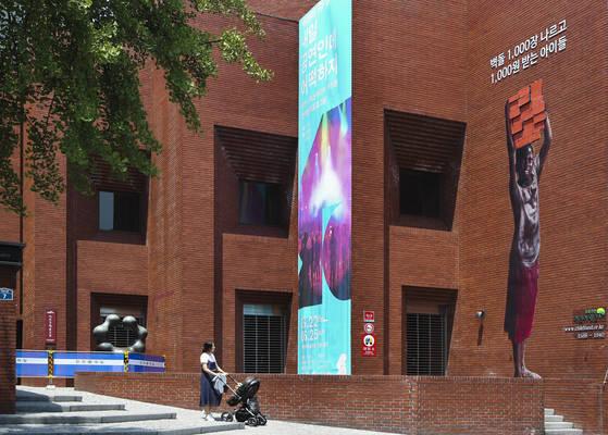 초록우산어린이재단이 아동노동 반대를 위한 캠페인을 벌이면서 서울 종로구 동숭동 아르코예술극장 외벽에 10m 길이의 벽돌노동아동 대형 사진을 부착했다. 신인섭 기자