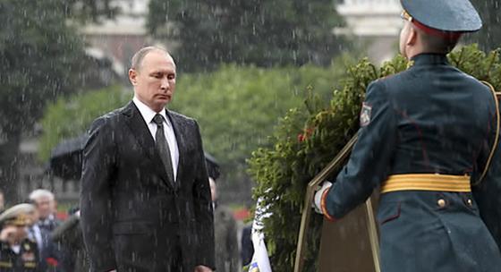 블라디미르 푸틴 러시아 대통령(왼쪽)이 22일(현지시간) 러시아의 현충일인 '추모와 애도의 날'을 맞아 모스크바 크렘린궁 옆 무명용사의 묘에서 우산을 접고 폭우를 맞으며 숙연한 표정으로 헌화 의식을 진행하고 있다. [모스크바 AP=연합뉴스]