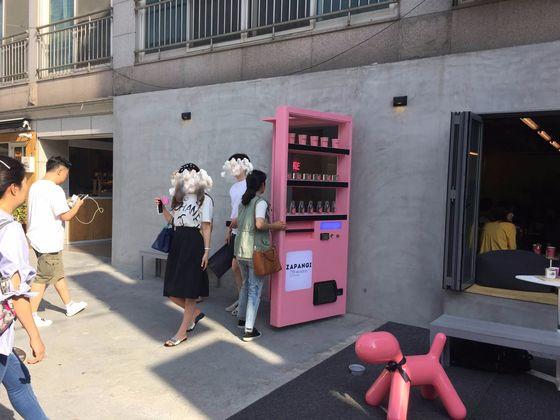 핑크색 자판기가 카페의 문. 자판기를 열고 사람들이 드나든다.