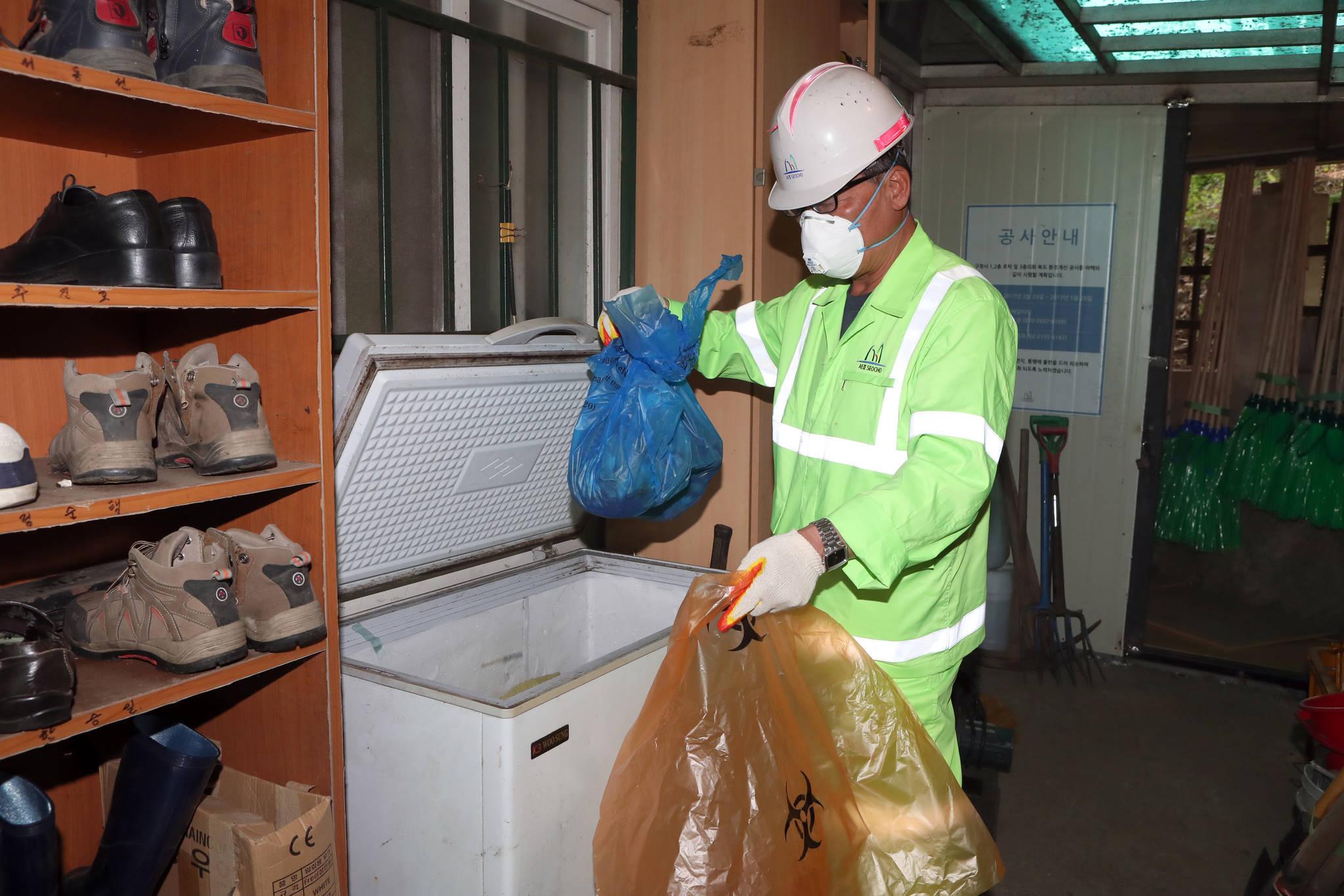 서울 서초구의 환경미화원이 23일 서초구 환경미화원 휴게소의 냉장고에서 동물들의 사체를 꺼내고 있다. 최정동 기자