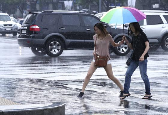 26일 오전 서울과 수도권지역에 반가운 비가 내렸다. 한 관광객이 서울 광화문사거리에서 고인 빗물을 조심스럽게 피해 길을 걷고 있다. 임현동 기자