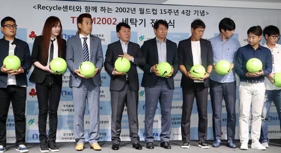 26일 서울 종로구 축구회관에서 열린 '리사이클 센터와 함께하는 팀2002 세탁기 전달식'에서 2002 월드컵 주역들의 모임인 '팀 2002(TEAM 2002)'회원들이 장애어린이들에게 전달할 사인볼을 들고 무대에 서있다. [연합뉴스]