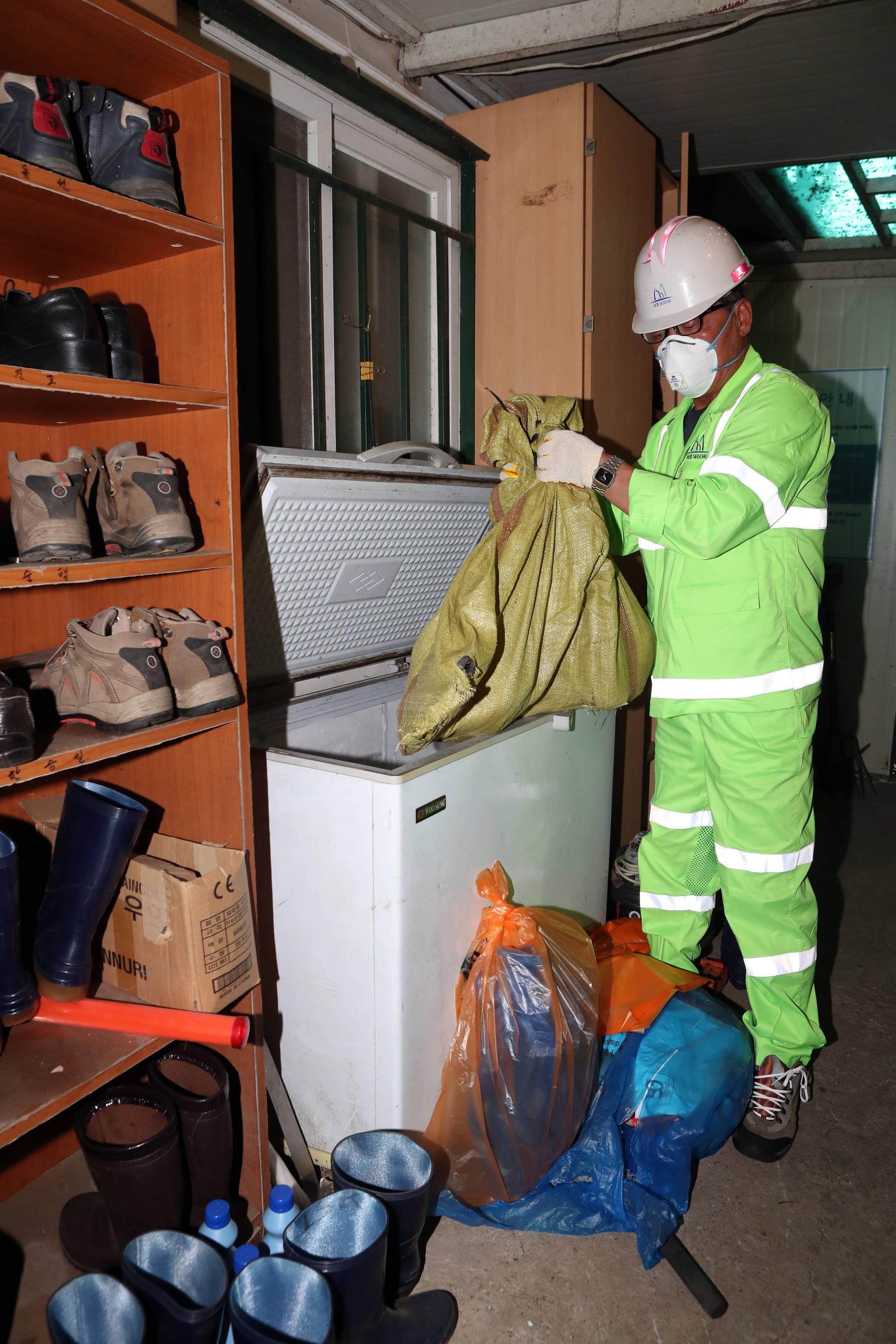 서울 서초구의 환경미화원이 23일 서초구 환경미회원 휴게소의 냉장고에서 동물들의 사체를 꺼내고 있다. 최정동 기자