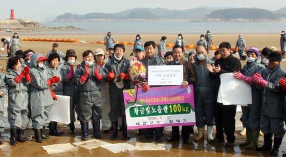 2008년 2월 태안 기름 유출 사고 현장에서자원봉사자 100만명 돌파를 기념한 행사가 마련됐다. [중앙포토]