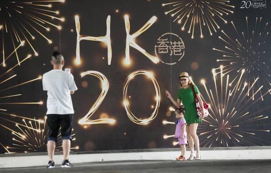홍콩의 주권 이양 20주년을 기념하는 광고판 앞에서 한 가족이 기념사진을 찍고 있다. [홍콩 EPA=연합뉴스]