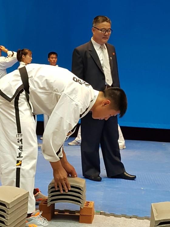 박영칠(검은 정장)ITF 태권도 시범단장이 26일 WTF와 합동 공연이 예정된 전북도청 공연장 무대를 살피고 있다.북한 선수들이 격파에 쓰일 기왓장을 점검하고 있다.전주=김준희 기자