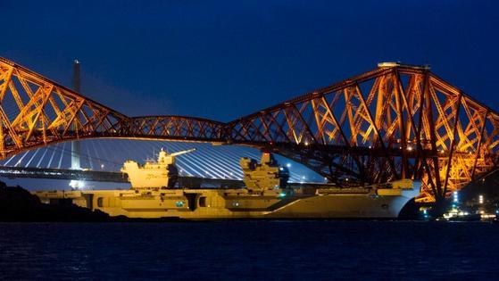 영국이 역대 최대 규모로 건조한 퀸 엘리자베스 항공모함이 첫 바다 시험 항해에 나서기 위해 조선소 인근 다리 밑을 지나고 있다. [더선 캡처]