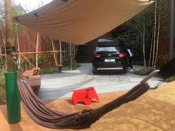 기아차가 29일 개관한 BEAT360 건물 뒷편 정원에 전시한 카니발 차량을 해먹에서 바라본 모습. 문희철 기자.