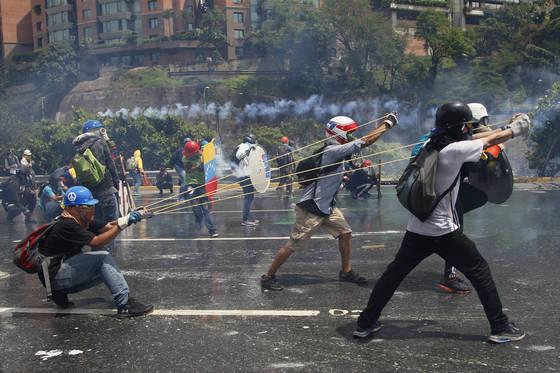 """""""최루탄 對 배설물 새총"""". 베네수엘라 수도 카라카스에서지난 3월 반정부 시위대가 최루탄을 쏘는 경찰을 향해 새총을 쏘고 있다. 새총으로 날린 병 안에는 배설물이 들어 있었다.  [AP=연합뉴스]"""