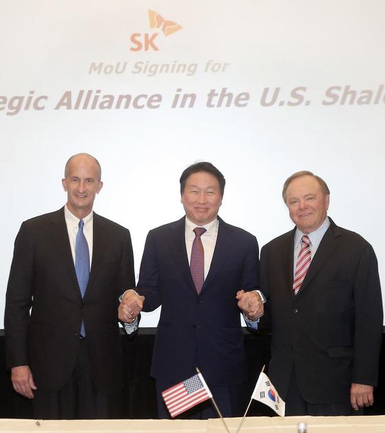 최태원 SK 회장(가운데)이 28일 워싱턴 세인트 레지스 호텔에서 GE 존 라이스(왼쪽) 부회장, 콘티넨탈 리소스의 헤럴드 햄(오른쪽) 회장과 전략적 제휴를 강화하기로 협의한 뒤 기념사진을 위해 포즈를 취하고 있다. [사진 SK]