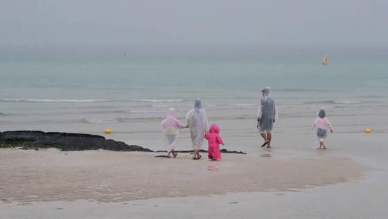 장맛비가 내리기 시작한 지난 29일 오전 제주시 한림읍 협재 해변을 찾은 관광객들이 모래밭을 걷고 있다. [연합뉴스]