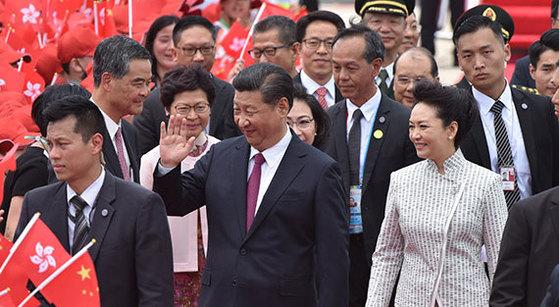29일 시진핑 중국 국가주석(가운데)과 부인 펑리위안이 홍콩 반환 20주년을 맞아 홍콩 국제공항에 도착해 환영 인파를 향해 손을 흔들고 있다. [AFP=연합뉴스]