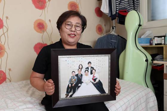 사춘기 '위탁 아들'을 돌보고 있는 송순향씨가 지난 6월 서울 노원구 자택에서 가족사진을 보여주고 있다. 가슴으로 낳은 아들 민호(가명 왼쪽)의 재산목록 1호인 첼로가 방에 놓여있다.최정동 기자