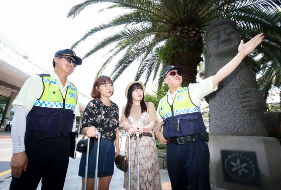 지난달 18일 제주국제공항에서 제주 자치경찰관들이 이곳을 찾은 관광객들에게 주차장과 렌터카 승강장 위치를 설명해주고 있다. [프리랜서 장정필]