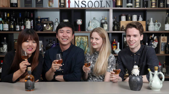 전통주 전문가 이지민씨와 '아몬드 스튜디오' 팀의 한국인 디자이너 조수아씨, 핀란드 출신 디자이너 밀라, 노르웨이 출신 디자이너 앨런드(왼쪽부터). 테이블위 세 병의 추성주 중 가장 왼쪽이 위스키 병을 연상시키는 새 제품이고, 나머지 두 개는 기존에 쓰였던 전통적인 디자인의 도자기 병이다. [강정현 기자]