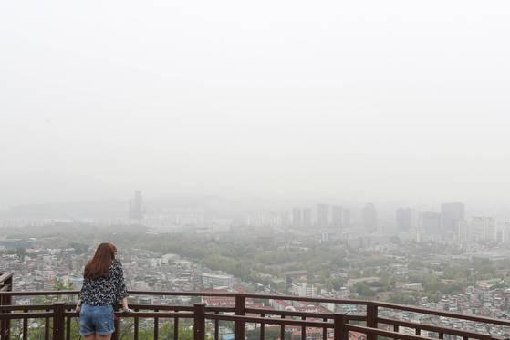 전국 13개 지역에 미세먼지 주의보가 발령된 지난 5월 8일 오후 서울 중구 남산에서 한 시민이 미세먼지로 뒤덮인 도심을 스마트폰 카메라로 찍고 있다. [중앙포토]
