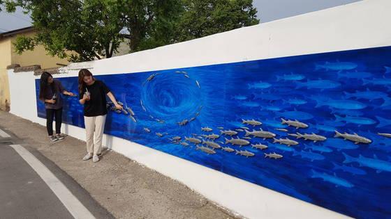 우수영문화마을 방문객들이 담장에 그린 작품 '울돌목=삶=Lifish'를 살펴보고 있다. [사진 해남군]