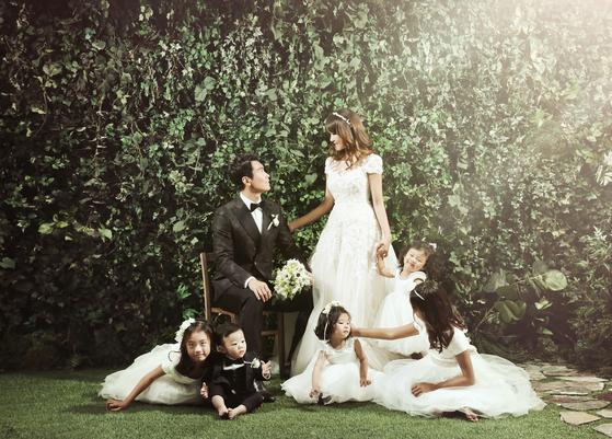 """2005년 미스 하와이 출신 이수진씨와 결혼한 이동국은 지난해 초 '결혼 10주년 리마인드 웨딩 화보'를 찍었다. 이동국은 """"10년 전에는 아내와 나 단둘이 찍었는데 이젠 5남매까지 7명이 됐다""""고 말했다. [사진 이동국 제공]"""
