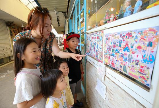 전주 남부시장 청년몰을 찾은 한 가족이 종이인형 등을 파는 가게를 구경하고 있다.[프리랜서 장정필]