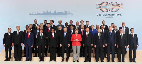 문재인 대통령을 비롯한 G20 각국 정상들이 7일 오후(현지시간) 주요 20개국(G20) 정상회의가 열리는 독일 함부르크 메세에서 기념촬영을 하고 있다.   앞줄 왼쪽부터 엠마누엘 마크롱 프랑스 대통령, 도널드 트럼프 미국 대통령, 조코 위도도 인도네시아 대통령, 엔리케 뻬냐 니에또 멕시코 대통령, 제이콥 게드레이레키사 주마 남아공 대통령, 마우리시오 마끄리 아르헨티나 대통령, 앙겔라 메르켈 독일 총리, 시진핑 중국 국가주석, 블라디미르 푸틴 러시아 대통령, 레젭 타입 에르도안 터키 대통령, 미세우 떼메르 브라질 대통령, 문재인 대통령. 둘째 줄 왼쪽부터 알파 콤데 기니 대통령, 파울로 젠틸로니 실베리 이탈리아 총리, 저스틴 트뤼도 캐나다 총리, 나렌드라 모디 인도 총리, 아베 신조 일본 총리, 말콤 턴불 호주 총리, 테레사 메이 영국 총리, 도날드 투스크 EU 정상회의 상임의장, 장 클로드 융커 EU 집행위원장. 세째 줄 왼쪽부터 안토니오 쿠테흐스 UN 사무총장, 에르나 솔베르그 노르웨이 총리, 마크 루터 네덜란드 총리, 마키 살 세네갈 대통령, 리센룽 싱가포르 총리, 마리아노 라호이 브레이 스페인 총리, 응웬 쑤언 푹 베트남 총리, 이브라힘 알아사프 사우디아라비아 재무장관, 앙헬 구리아 OECD 사무총장. 네째 줄 왼쪽부터 호베르토 아제베도 WTO사무총장, 테드로스 아디아놈 WHO 사무총장, 크리스틴 라가르드 IMF 총재, 가이 라이더 ILO 사무총장, 김용 세계은행 총재, 마크 카니 FSB 의장.김성룡 기자