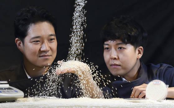 """BGF리테일 상품개발팀장인 조성욱(43·왼쪽)씨는 '밥 소믈리에'다. 조씨는 """"맛있는 밥을 지으려면 최근에 도정한 쌀을 선택하고 재배 지역이나 품종을 살피면 된다""""고 조언한다. 조씨가 간편식을 함께 연구하는 염준 대리와 쌀의 상태를 점검하고 있다. [임현동 기자]"""