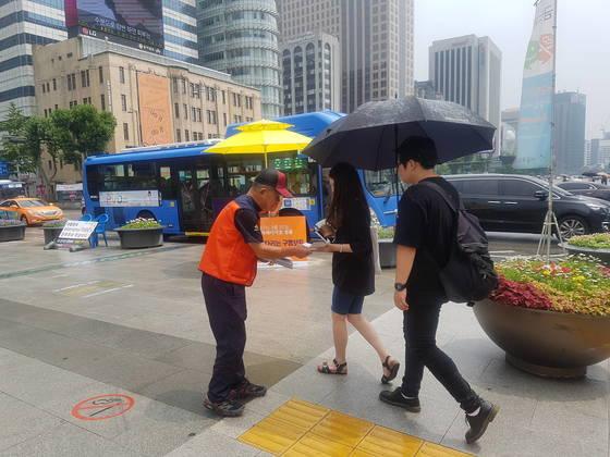 9일 오후스텔라데이지호 실종자 가족이장맛비를 맞으며 시민들에게 안내 전단을 나눠주고 있다. 송우영 기자