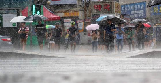 장마전선이 전국에 영향을 미치고 있는 9일 오후 서울 동작구 노량진역 앞에서 시민들이 비를 피해 발걸음을 옮기고 있다. [연합뉴스]