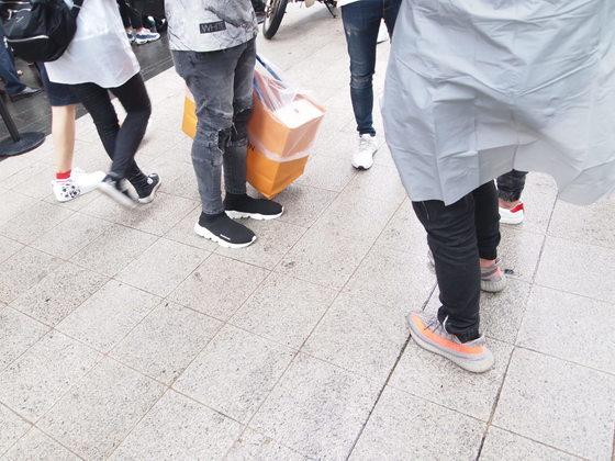 지난 7일에 포착한 청담동 루이비통 매장 앞. 루이비통 쇼핑백을 든 남성이 신은 신발이 발렌시아가 삭스 슈즈, 사진의 오른쪽 남성이 신은 제품이 아디다스 이지부스트다. 유지연 기자.