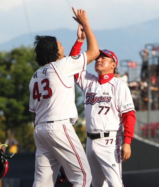 김기태 KIA 감독(오른쪽)은 선수와 함께 호흡을 맞춘다. 외국인 투수 헥터가 이길 땐 손가락을 하늘로 치켜올리는 세리머리를 함께 한다.[중앙포토]