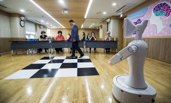 지난 10일 서울 삼성동 강남구 치매지원센터에서 노인들이 로벗의 목소리에 따라 치매예방 프로그램에 참가하고 있다. 박종근 기자
